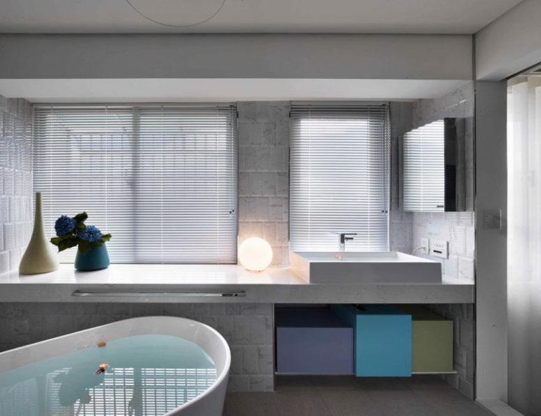 Master bathroom is clean and simple, with colorful geometric boxes for storage
