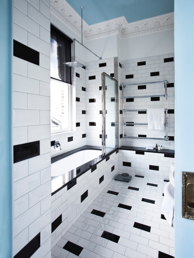 The master bathroom is done in black and white but the ceiling ties it with the rest of the apartment