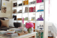 12 a tall shelving unit separates a bedroom zone from the living room