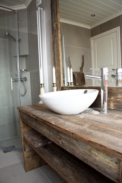 a modern bathroom with a countertop and mirror frame from recycled materials