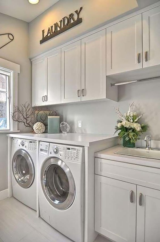cabinets all over the laundry is a grey way to keep it uncluttered, keep them light-colored to visually expand the space