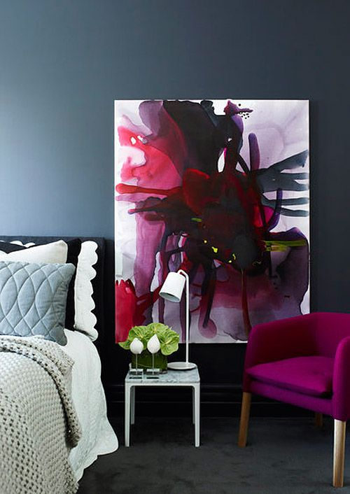 this bedroom is enlivened with a fuchsia chair and a unique wall art