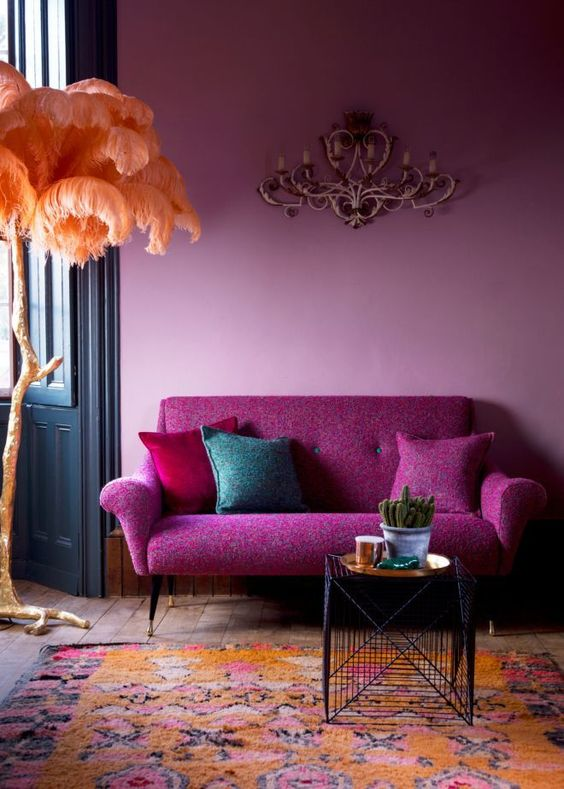 mid-century styled sofa in fuchsia color and a light pink wall look harmonious together