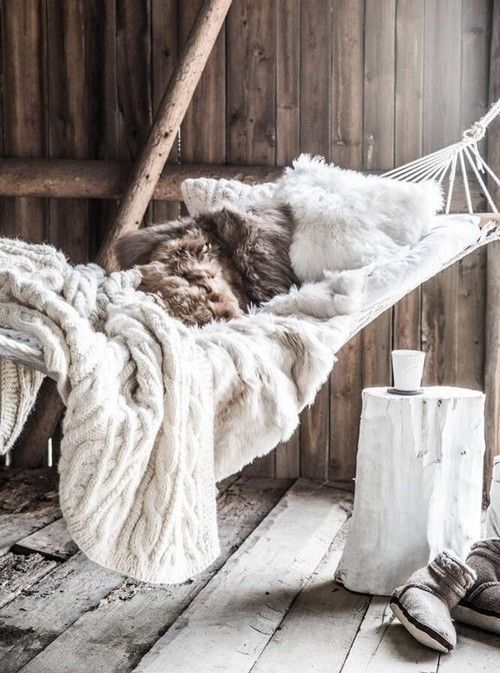 hammock with fur pillows and a cable knit blanket