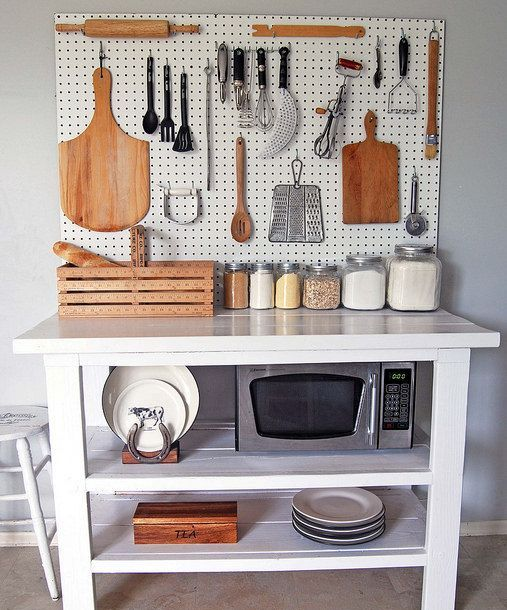 kitchen island with a white pegboard for storage