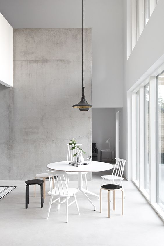 minimalist space with a concrete accent wall and lots of whites