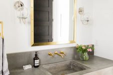 17 brass mirror frame and faucets add a glam feel to this bathroom