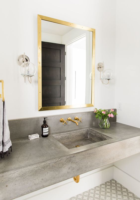 brass mirror frame and faucets add a glam feel to this bathroom