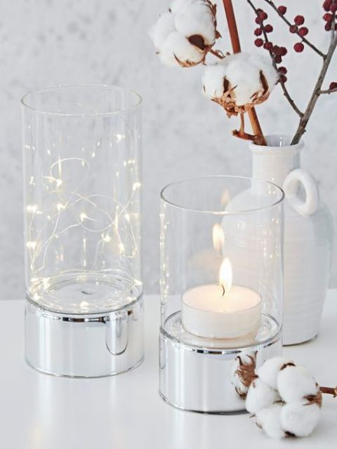 clear glass hurricanes with silver bases can add a cool touch to any decor