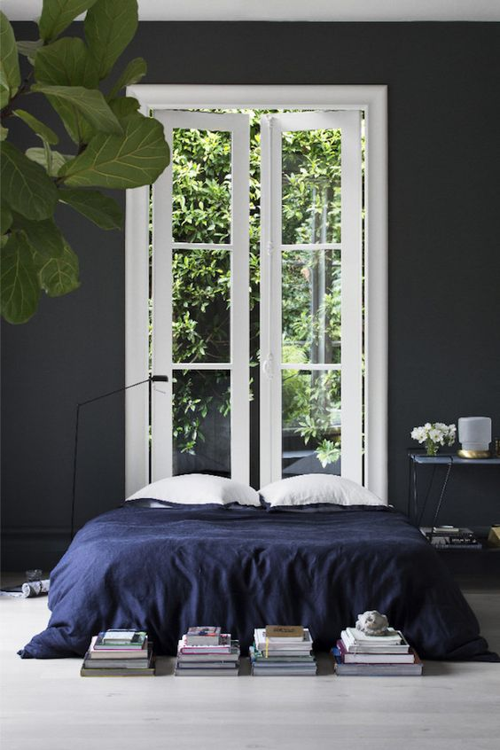 indigo bedspead in a dark and moody bedroom is a nice idea