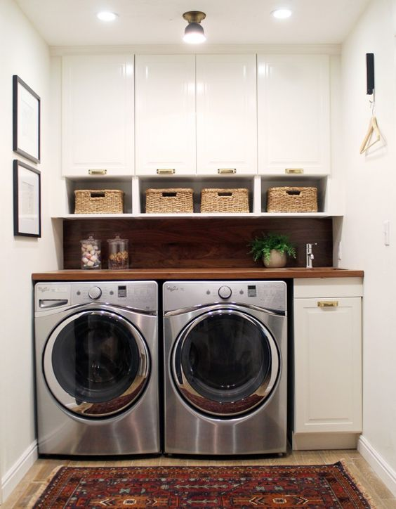 small laundry organized with cabinets and baskets for smaller items