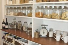24 glass containers with lids and baskets for other stuff underneath