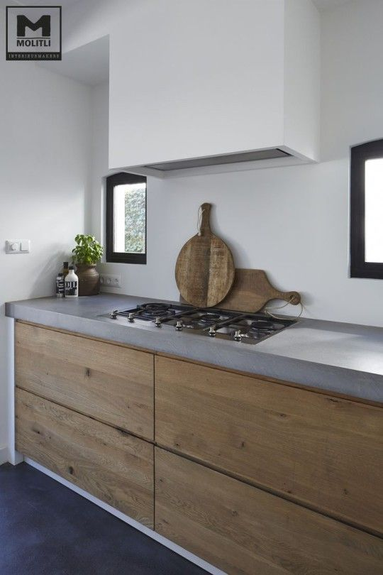 minimalist kitchen with concrete countertops and warm wood drawers