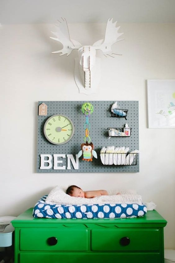 a pegboard in a nursery over the diaper changing station is a very practical solution