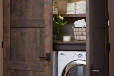26 barnwood doors hide a laundry nook and echo with the shelves inside