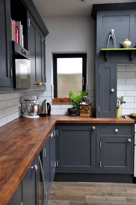 dark grey kitchen cabinets and dark stained butcher block countertops