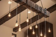 27 rough wood ceiling beams and an industrial chandelier with bulbs perfectly add texture