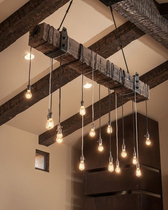 rough wood ceiling beams and an industrial chandelier with bulbs perfectly add texture