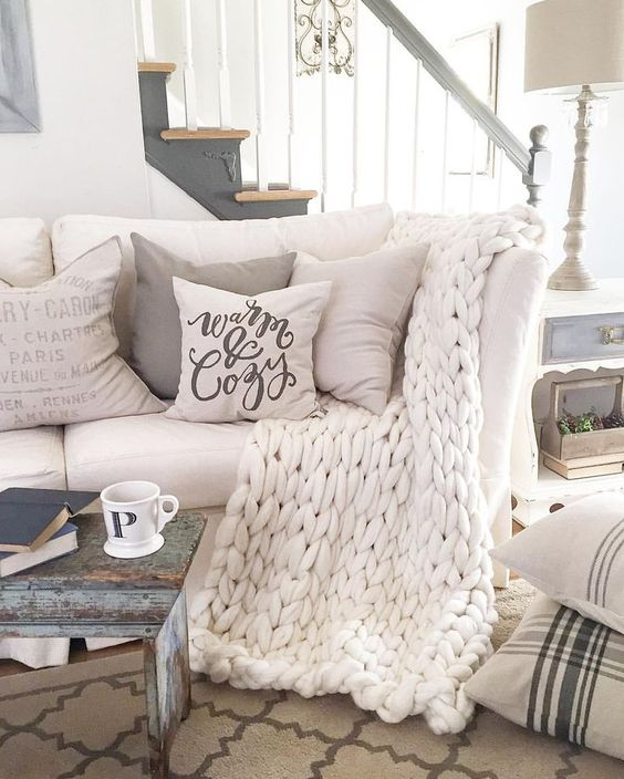 cozy white sofa with neutral pillows and a white chunky knit blanket