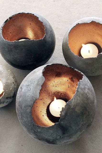 concrete spheres with metallics inside as candle holders