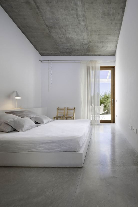 pure white bedroom with an accent concrete ceiling