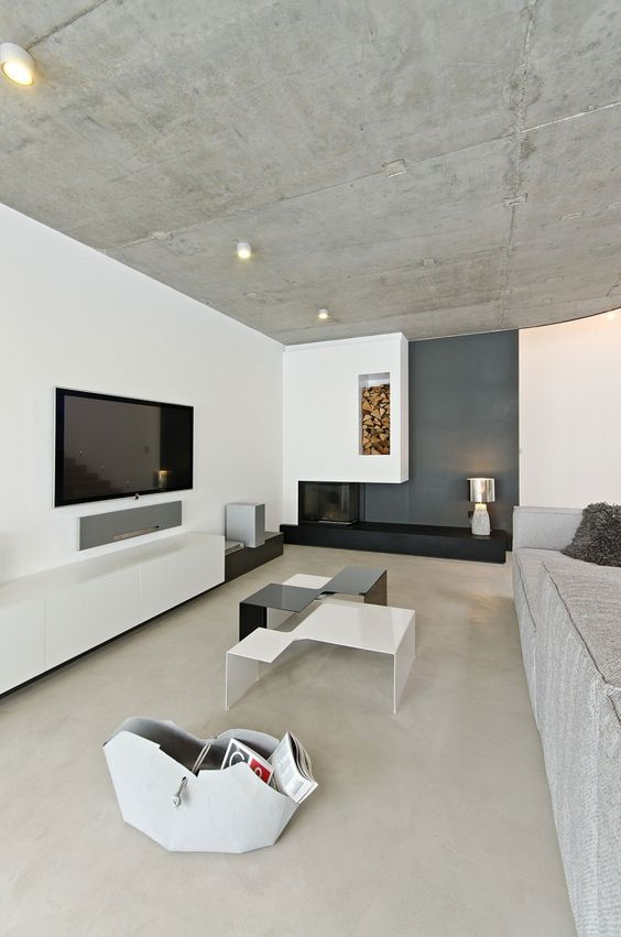 minimalist living room with a concrete ceiling and white walls