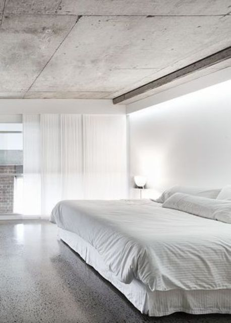 minimalist bedroom with polished concrete floors and a concrete ceiling