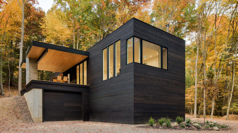 This forest cabin in blackened wood was built for a car lover owner
