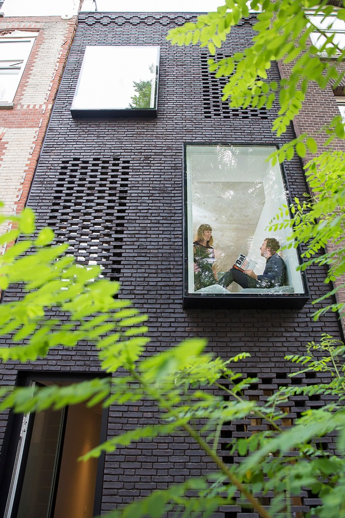 This modern black brick house is tightened between two old residences and was built by two architects for themselves