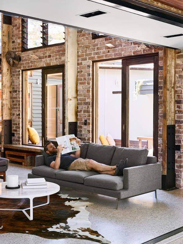 The living space features brick walls, wooden rustic beams that support the ceiling and a cool animal skin rug, the furniture itself is rather neutral