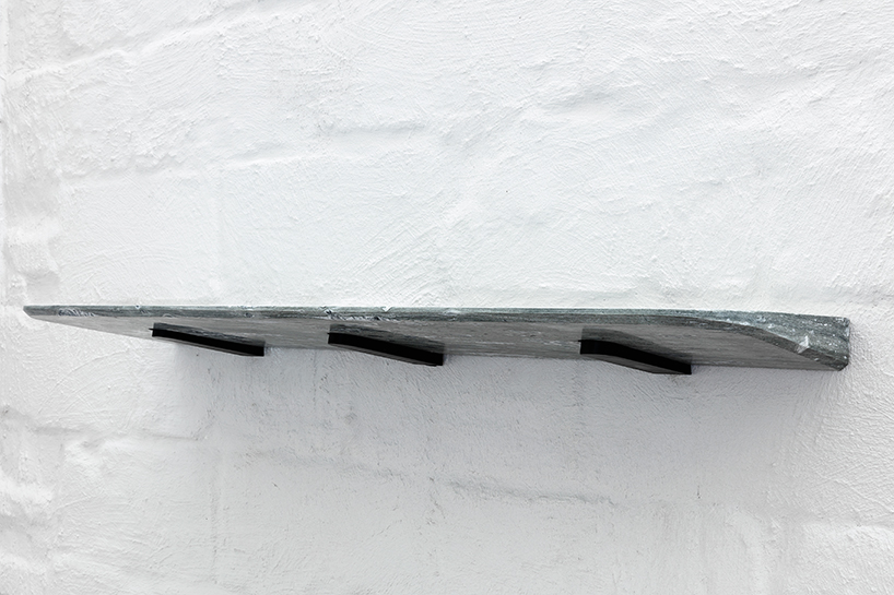The marble is precisely fixed to three small wedges that fasten to the wall, locking into the stone using only gravity