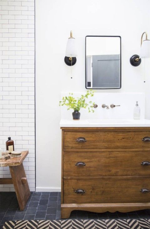 a wooden sideboard turned into a rustic bathroom vanity