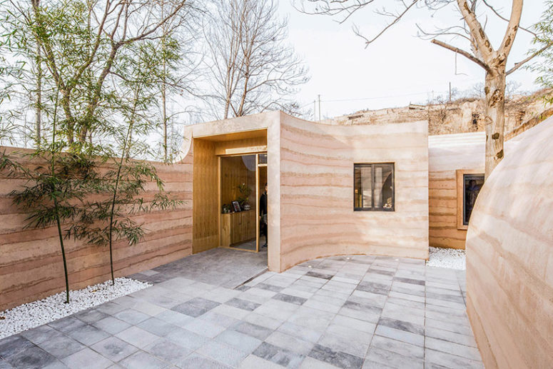 Grey tiles cover the courtyard and gravel defines the plants