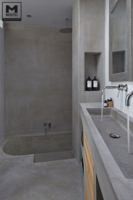 an all-concrete bathroom with the same vanity and wooden details