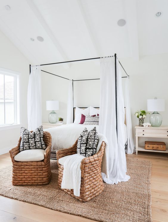 beach-inspired bedroom with a thin metal frae bed and airy white curtains
