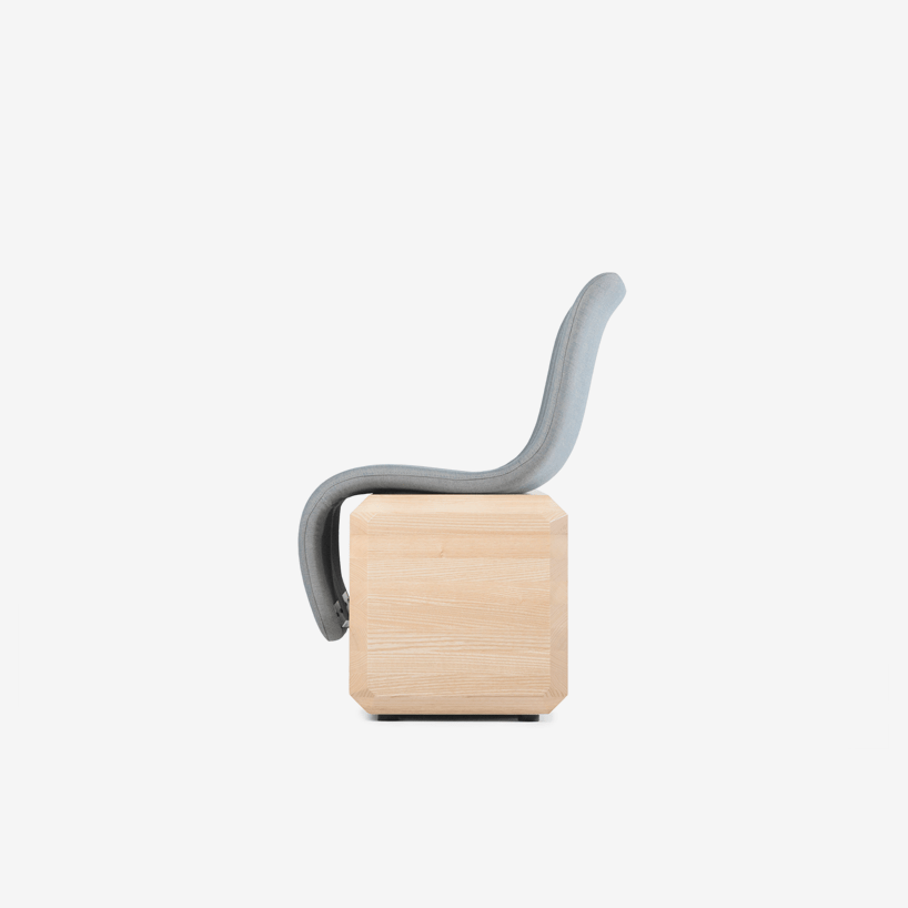 The design includes a sharp contrast between the organic profile of the seat and the geometric sturdy base