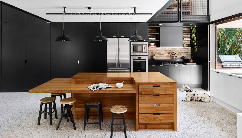 The kitchen is a modern sleek one, all the handles hidden and done in black, with a cool sculptural kitchen island