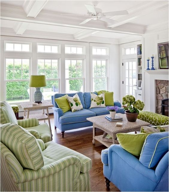 shades of green and blue in this living room are complemented with white and beige for a cozy feel