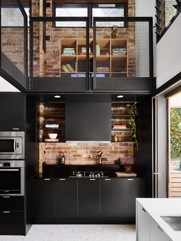 The brick backsplash creates a cool contrast with sleek black panels