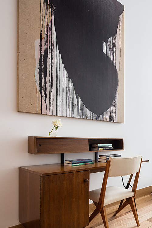 The home office nook features mid-century modern desk with sotrage and another eye-catchy work of art