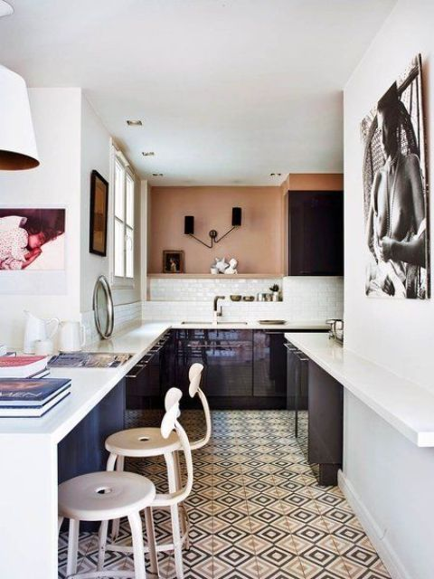 The kitchen is modern and sleek, in very dark purple and with contrasting white countertops, and an African woman portrait reminds of the boho feel