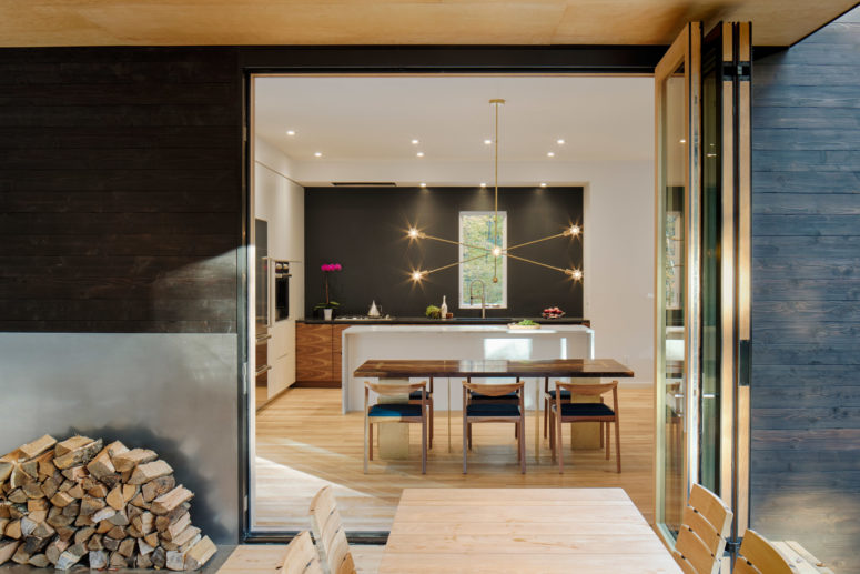 The kitchen is modern, black and white, with a waterfall kitchen island and a cool pendant lamp