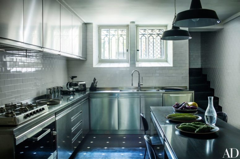 The kitchen is modern, with simple white tiles and stainless steel cabinets and appliances, the lamps are vintage ones