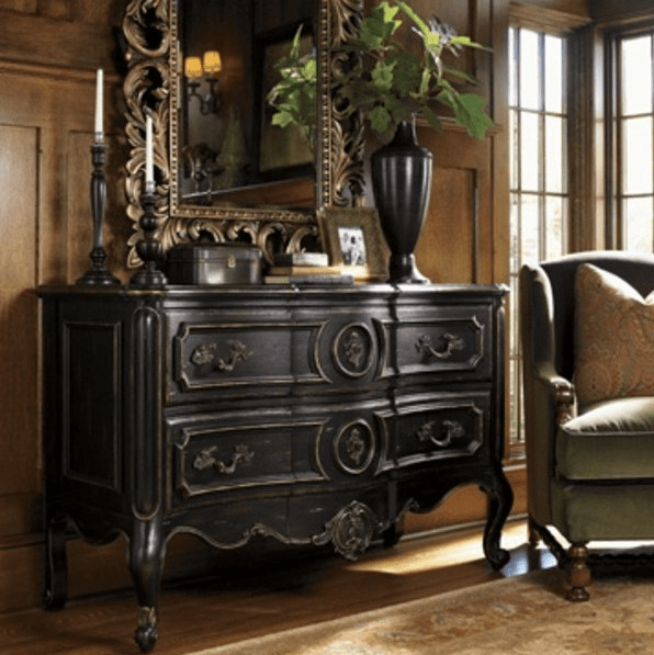 a dark wood sideboard with antique decor, a mirror and a dark vase