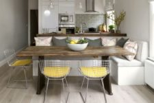 05 modern white sleek kitchen with grey tiles and a dining space with metal wire chairs grey pillows to echo