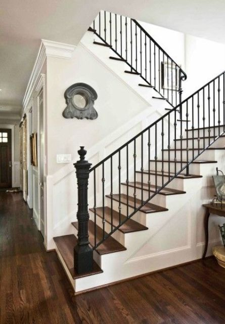 Sharp Looking Staircase With Metal Posts And Wrought Iron Railing