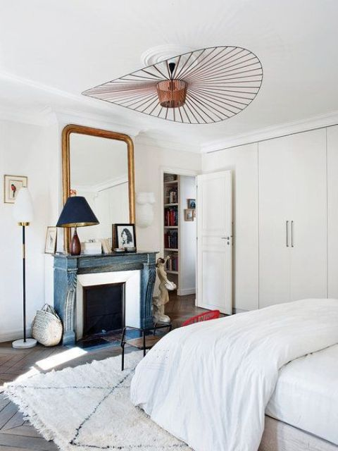 The focal point of the bedroom is the turquoise shabby chic fireplace with an oversized antique mirror over it