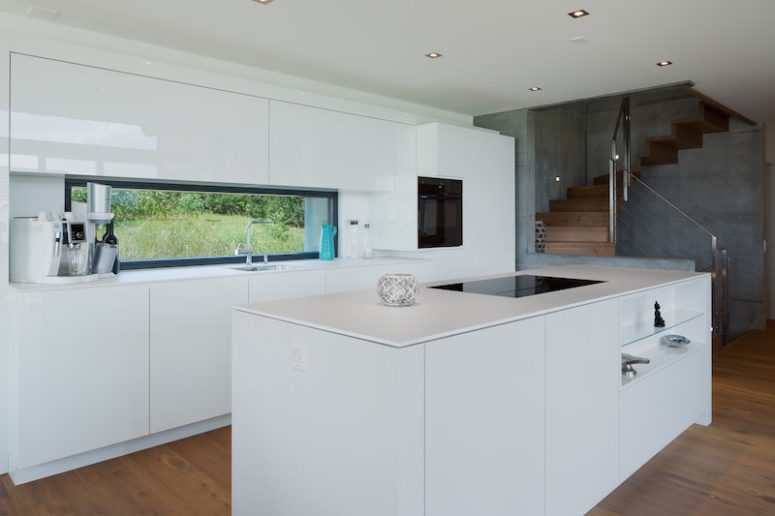 The kitchen is done in white, everything possible is hidden for a sleek look and there's a window instead of a backsplash