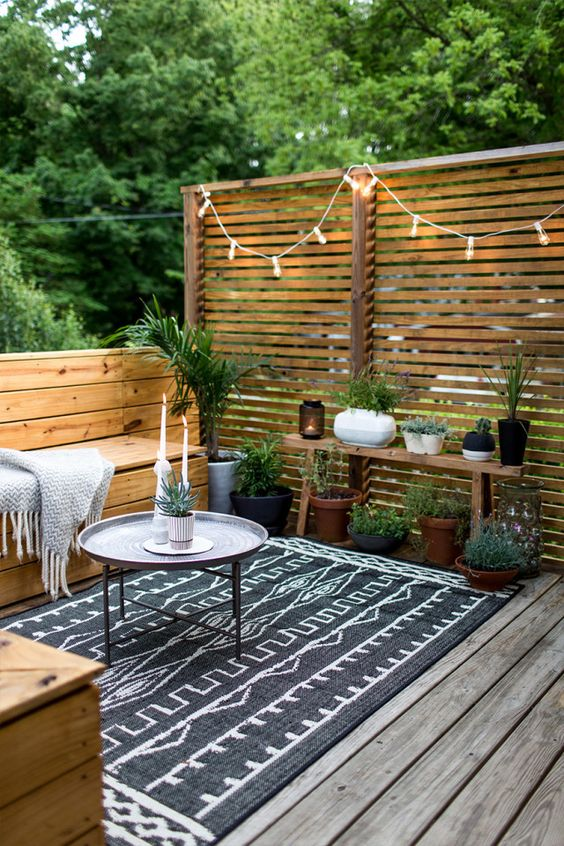 cozy deck with a wooden fence with lights and corresponding wooden furniture