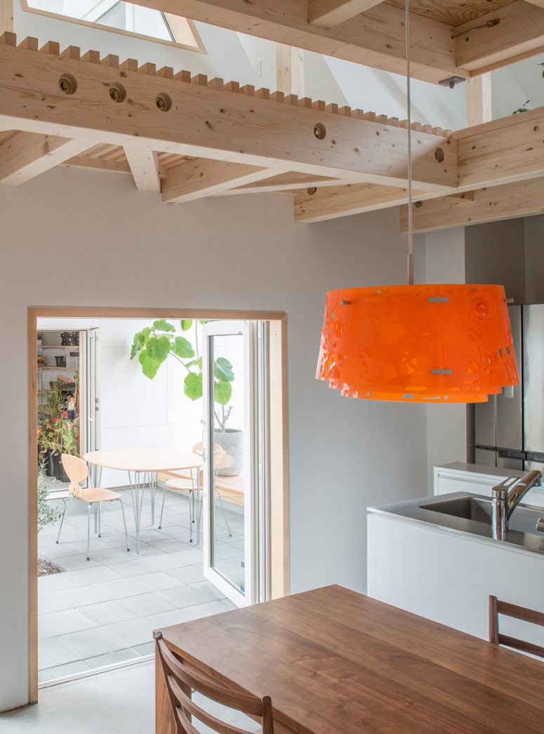 the kitchen is minimalist, with white cabinets, stainless steel surfaces and a warm woods, there's an eye-catchy bold pendant lamp